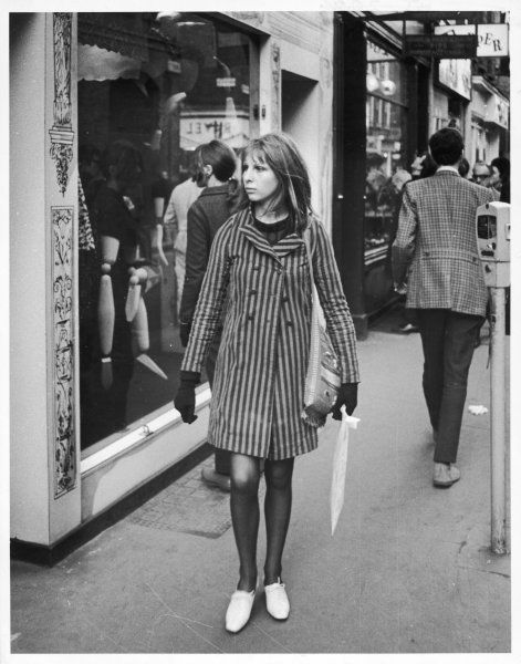 A fashionable girl walks down Carnaby Street, London, in her stripy mini overcoat and gloves