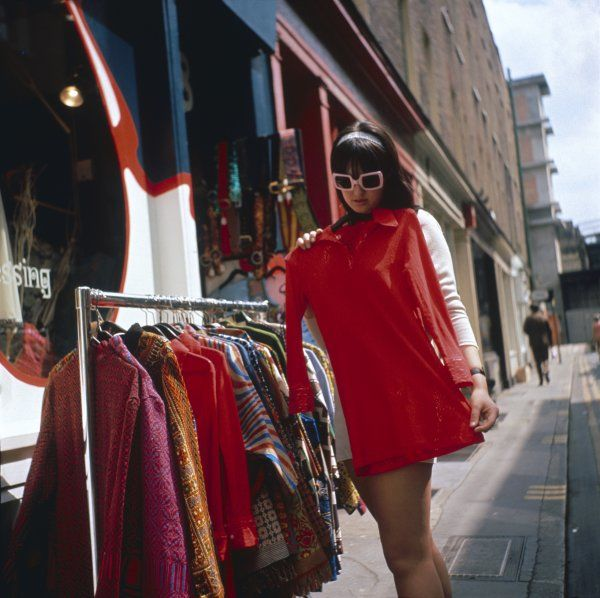 "A ""hip chick"" in sunglasses chooses a red mini dress from a rack of colourful outfits"