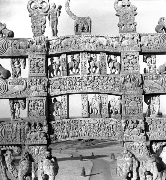 An ornately carved gateway to the Stupa at Sanchi, a small village in the province of Madhya Pradesh, Central India. The Stupa is a large hemispherical dome with a central chamber containing relics of the Buddha. Photograph by Ralph Ponsonby Watts