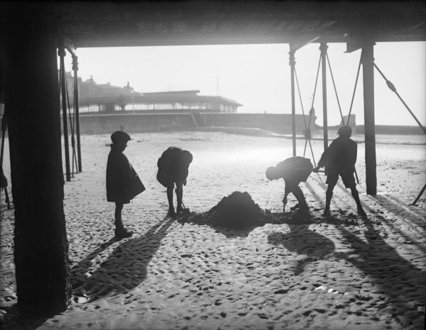 Four children make a sandcastle under the pier at Ryde, Isle of Wight, England