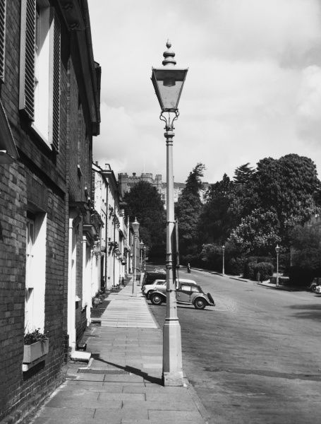A view up Castle Street in Farnham, Surrey with parked cars and street lamps
