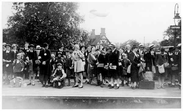 A group of excited evacuee schoolchildren wait with their nurses on the platform of Catford train station in south east London. (Note the barrage balloon behind them)