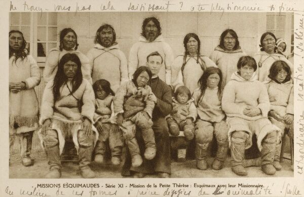 Catholic Mission to the Inuit - Newfoundland and Inuit. A group of Inuit men, women and children and the Catholic Priest of the Mission (centre). Date: circa 1920s