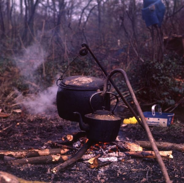 A cauldron and a kettle heating over a log fire in the open air at a gipsy encampment