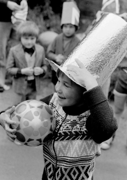 A small boy, holding a ball and wearing a handmade foil-covered top hat, smiles cheekily during a street party in Essex in honour of the Silver Jubilee of Queen Elizabeth II. 1977