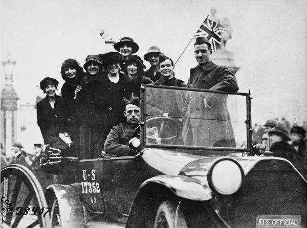 Women riding in a car with American soldiers celebrating the end of World War I in 1918