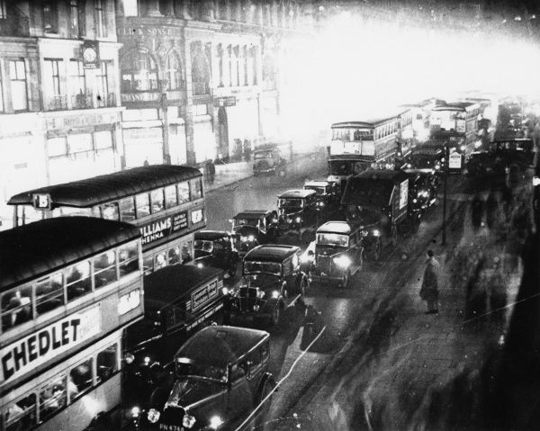 A view of a Central London street by night, with buses and cars