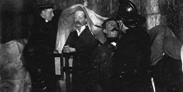 Wax models of Dr Crippen and other criminals from the Chamber of Horrors being covered with tarpaulins by salvage men after suffering water damage after fire ravaged the Madame Tussauds waxworks exhibition in the building on Marylebone Road