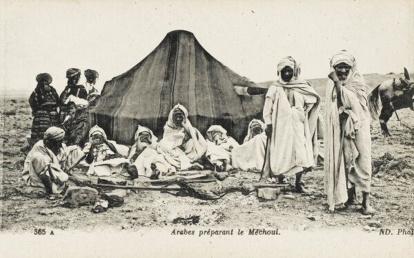 Chaouis Berber Camp - Algeria. Barbequeing a goat. The men sit and stand in the foreground close to the fire, whilst the women stand at the rear close to the low camel-hair tent. The Chaouis are a Berber people who live mainly in the Aurs Region