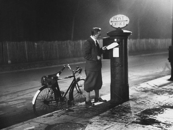 A smart cyclist stops to pop a letter into a Royal Mail letterbox