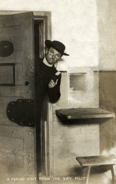 The prison chaplain, jocularly referred to as the 'sky pilot', visits a cell at Wakefield Prison, West Yorkshire. The prison was originally built as a House of Correction in 1594