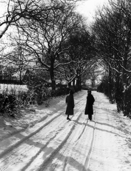 Getting the gossip - two people stop for a chat on a snowy winter's morning in a country lane in Essex, England. Date: 1950s