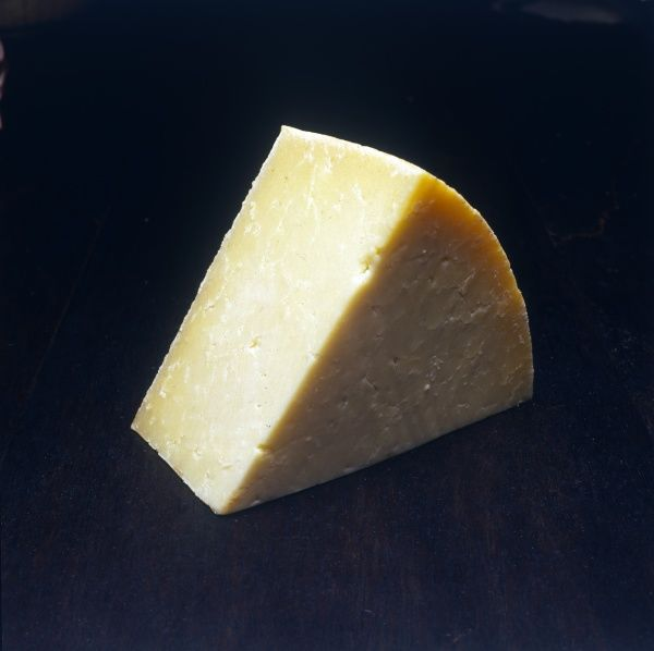 A wedge of English Cheddar cheese. Date: 1980
