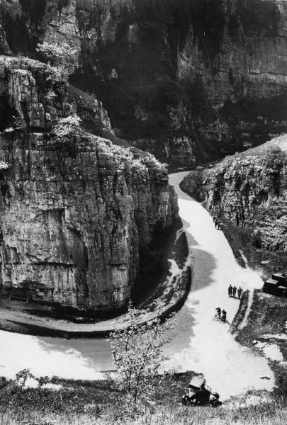 A striking view of the road winding around the famous hairpin bend in Cheddar Gorge, Somerset, England. The towering limestone cliffs and crags rise some 450 feet high. Date: 1930s