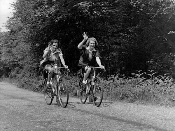 Two charming lady cyclists, waving 'Cheerio' to us as they cycle by! Date: 1930s
