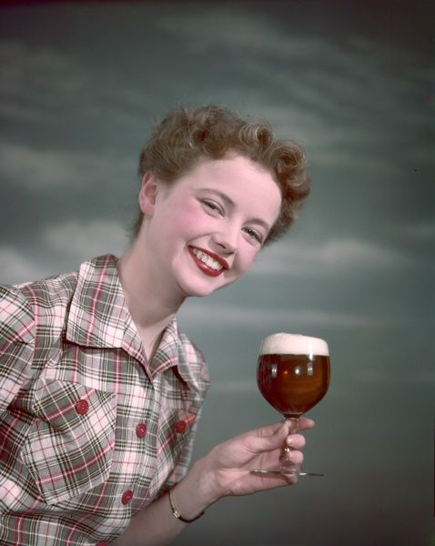 Smiling model with perfect teeth holds up a glass of foaming beer with a very large head on it. No wonder she looks so happy