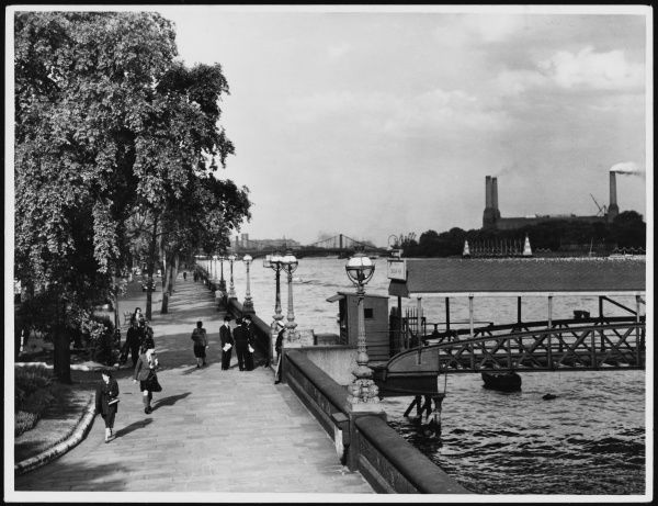 Walking past the pier on Chelsea Embankment in London. Battersea Power Station can be seen in the background