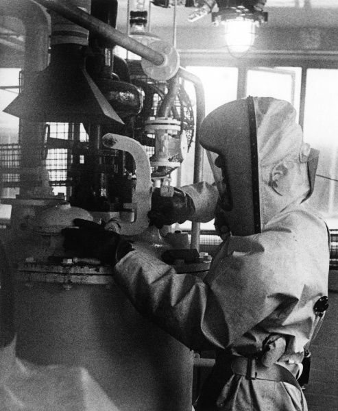 A worker wearing a protective suit in a chemical factory. Date: 1950s