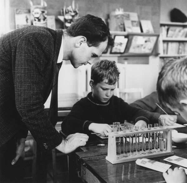 A male teacher leans over a group of schoolboys as he explains something to them during a Chemistry lesson at Nuffield Junior School, London. Date: 1960s