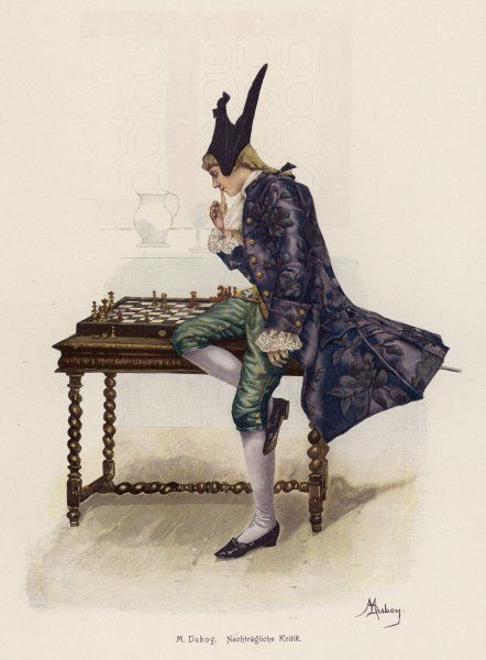 A smartly-dressed young man studies the pieces on a chessboard
