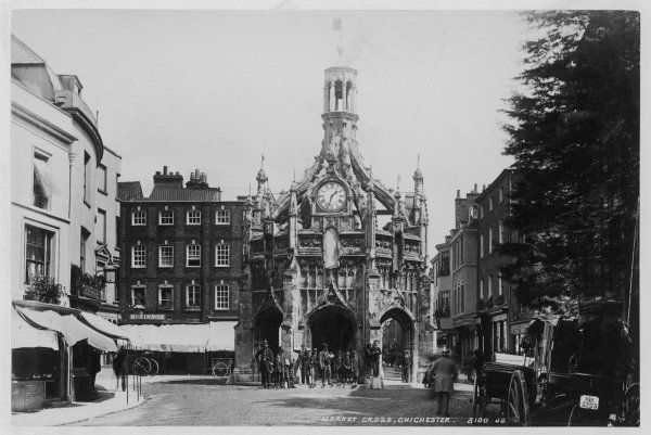 The Market Cross at Chichester, West Sussex, at 1.30pm : a helpful policeman is holding back pedestrians while the gentleman takes his picture