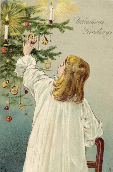 A girl hangs decorations on the tree - or is she helping herself to them ?