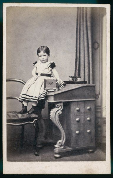A small child wears a frock with short sleeves ornamented with full rosettes of narrow ribbon, volans & ribbon trim on the skirt, broad belt with buckle & button boots