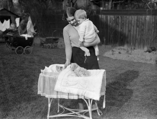 A young mother introduces her young son to his new baby brother or sister in a cot. Date: 1930s