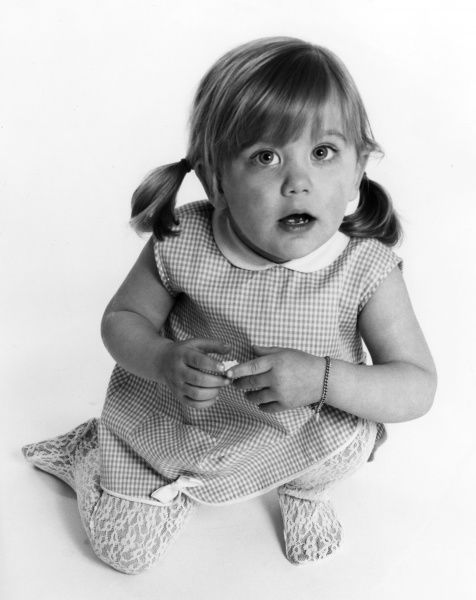 A little girl poses for the camera. Date: late 1960s