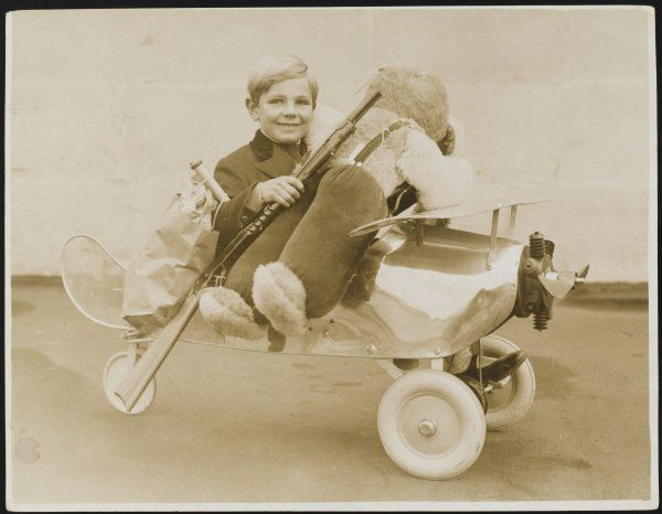 A young boy sits in the latest toy - a pedal-driven aero- tricycle with a clockwork propellor. This toy is guaranteed to keep children happy at Christmas