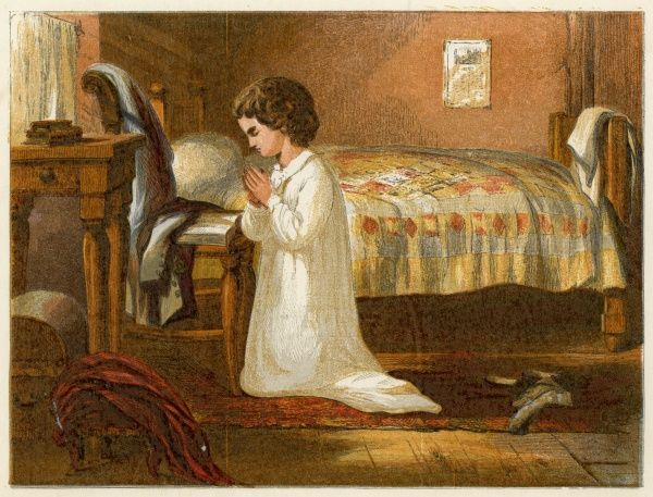 A child kneels in prayer at the side of the bed