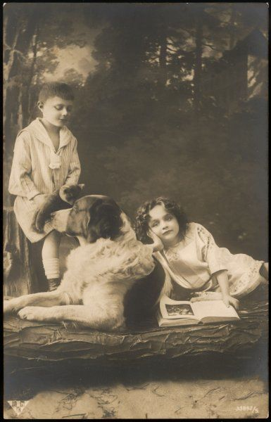 Two French children pose with a very large dog - very likely a Newfoundland. The girl sits with a book