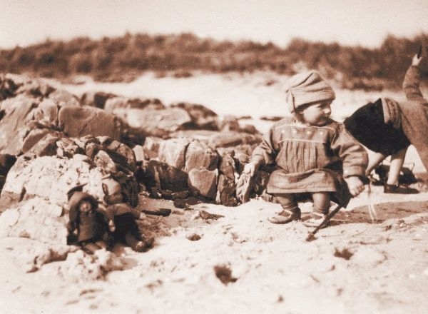 Two little children with their dolls on a beach, somewhere in Scotland