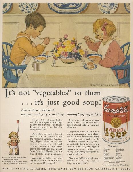 Two children, neatly dressed, and with napkins around their necks tuck in enthusiastically to a steaming bowl of Campbell's vegetable soup