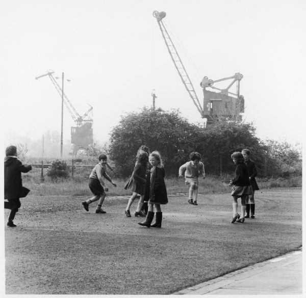 Children playing in an East Glasgow street with some building machinery in the background