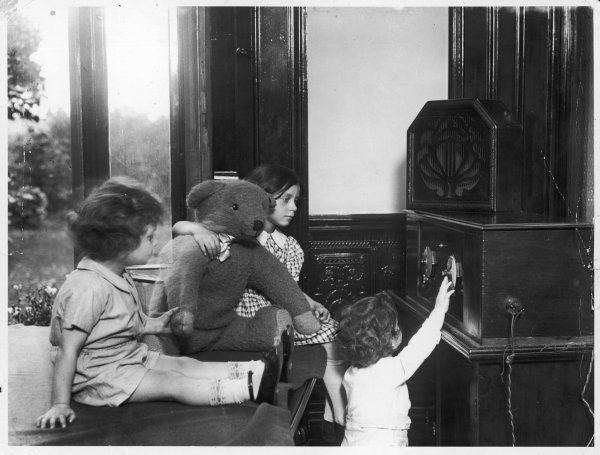 Three children at the 'Babies Hotel', Clapham Common, London, listen intently to the radio at home, whilst Teddy seems distracted