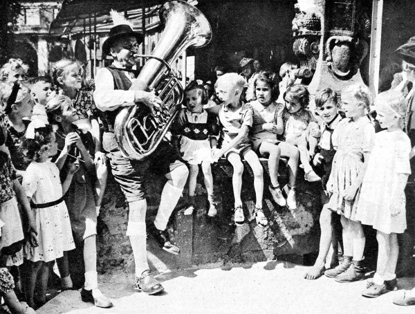 Photograph showing a group of children listening to a man playing a tuba in Berlin, just after the end of the Second World War in Europe, August 1945