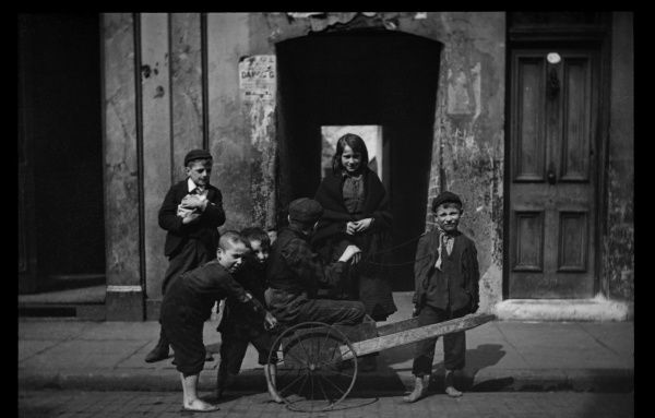 Six children with a makeshift cart, on a scruffy terraced street in London. Two of the boys have bare feet