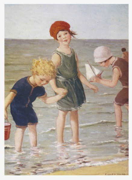 Three children paddling in the sea; one carries a bucket, another inspects a toy boat