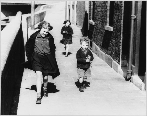 Three young children walk along a pavement on a blustery day