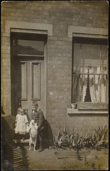 Two children, who appear to be brother and sister, shown playing with their Jack Russell, by the front door of their house. The window has net curtains and a window box