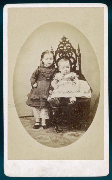 Baby wears an embroidered frock. The little girl wears trousers ornamented with tucks showing below the flounced skirt of her dress & leather shoes with a bar
