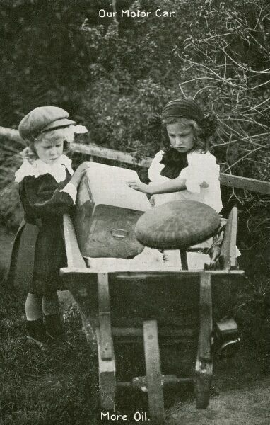 Two young children convert the family wheelbarrow into a far more exciting pretend 'Motor Car'. Here they are loading up the oil and they have already fashioned a steering wheel from a piece of garden furniture (or lampshade?)