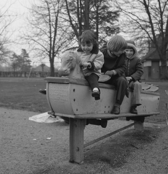 Three children on a playground ride with a row of seats and a horse's head at the front