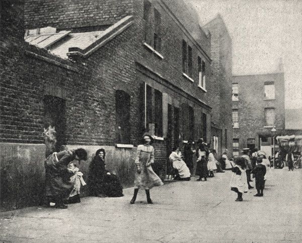 Children playing in front of houses in the East End of London. A few women are sitting on chairs, chatting