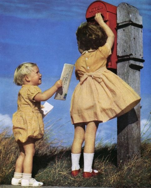Two children, dressed in adorable matching yellow outfits, post a letter at a rather remote looking postbox. Date: 1951
