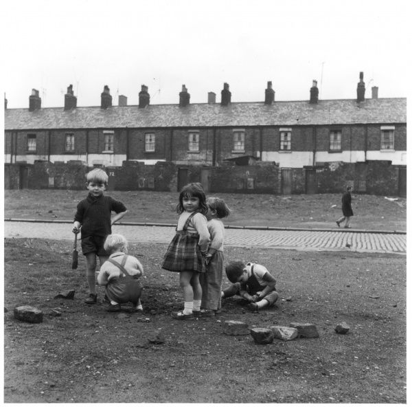 Children playing amongst rubble in front of a row of terraced houses in Liverpool