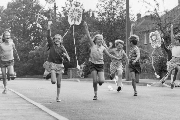 A group of children in Horley, Surrey, running along a street with their kites, having a wonderful time