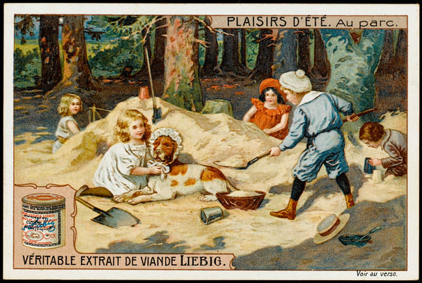 Children play in a sandpit in a park; a little boy digs, whilst a young girl ties a bonnet around her dog's head