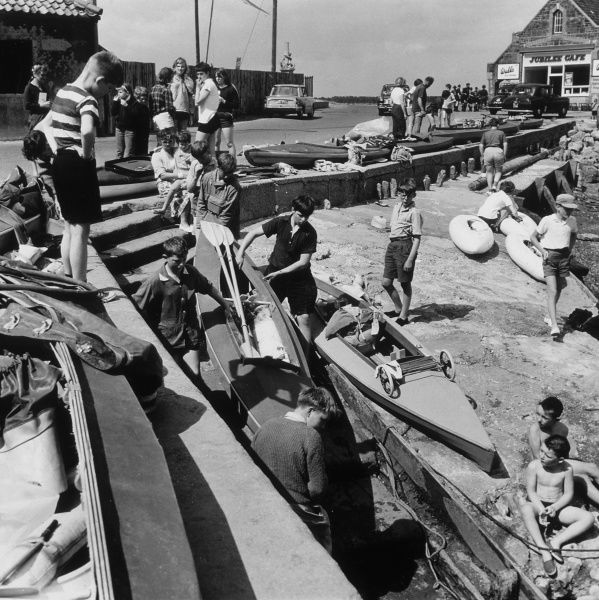Boys at the seaside, getting ready to take the boats out. Date: 1964